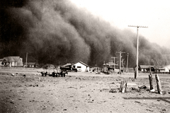 A dust storm is seen passing over homes in a rural area