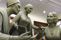 A sculpture-in-progress shows Sojourner Truth, Susan B. Anthony, and Elizabeth Cady Stanton gathered in conversation.