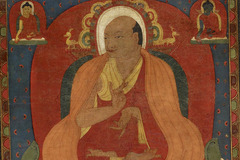 painting of a yoga teacher wearing robes and sitting cross legged with smaller portraits of women in robes above him